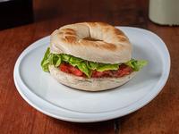 Sándwich de pan bagel, salmón ahumado, lechuga, palta y queso philadelphia