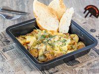 Papines asados con hierbas, pepinillos y queso raclette