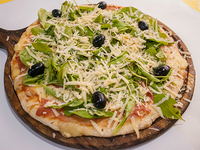 Pizza con jamón crudo, rúcula y parmesano