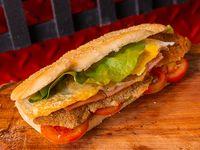 Sándwich de milanesa con jamón, queso, lechuga, tomate y huevo