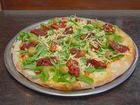 Pizza de mozzarella, tomates secos y rúcula