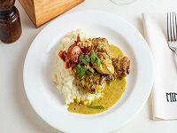Pollo al curry con risotto al vino blanco, posciutto y nueces tostadas