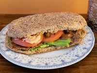 Sándwich de lomito de seitan en pan integral con mayonesa de albahaca, tomate y lechuga.