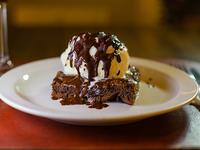 Brownie con helado de crema y salsa de chocolate