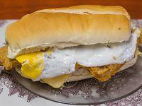 Sándwich de milanesa gigante con lechuga, tomate, queso y huevo acompañamiento de Papas Fritas