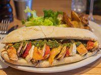 Sándwich de pollo asado con hongos portobello, queso brie, tomates secos y pesto acompañado con papas doradas al horno