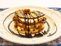 Torre de pancake con bananas , dulce de leche, chocolate derretido y crema Chantilly