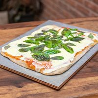 Pizza con hojas de albahaca