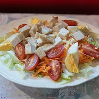 Ensalada de lechuga, tomates cherry, zanahoria, huevo, queso parmesano y pollo