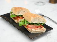 Panino de salmón, queso crema, tomate, pepino y rúcula
