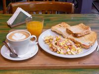 Promo - Café con leche o té, jugo de naranja, huevos revueltos con bacon y tostado de pan negro