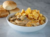 Porción de pollo al champignon con papas parmantier