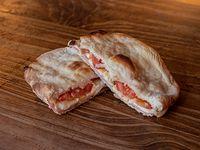 Sándwich de pan de pizza con jamón, queso y tomate
