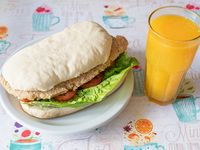 Combo - Exprimido de naranja + sándwich milanesa de pollo con lechuga y tomate en pan casero