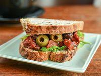 Pan de nuez, olivas marinadas, queso blanco, rúcula, tomates asados