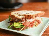 Pan de nuez, jamón crudo, queso blanco, tomates asados, rúcula, aceite de oliva
