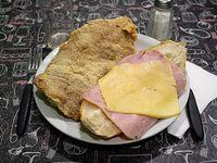 Sándwich de milanesa con jamón, queso y fritas chicas
