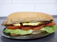 Sándwich de milanesa con lechuga, tomate y huevo