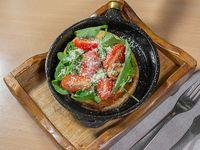 Provoleta grillada con rúcula y tomate