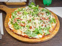 Pizza con rúcula, tomate secos, parmesano y crudo