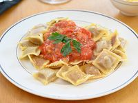 Ravioles artesanales rellenos de Ricotta, con salsa a elección, Parmesano y Pan